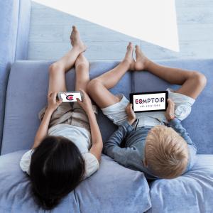 Deux enfants sur un canapé avec un smartphone et une tablette avec le logo du comptoir à l'intérieur