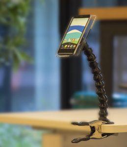 Un bras articulé de handieasy avec un smartphone accroché sur une table