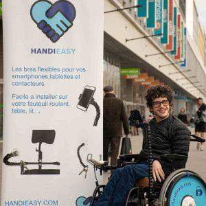 Jason Chemama dans son fauteuil et face à son kakémono de son entreprise Handieasy