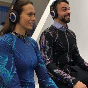 Deux personnes testant la combinaison Soundshirt avec un casque sur les oreilles