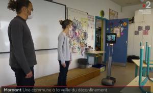Deux personnes dans une classe devant un tableau avec le robot Awabot utilisé par quelqu'un de chez soit