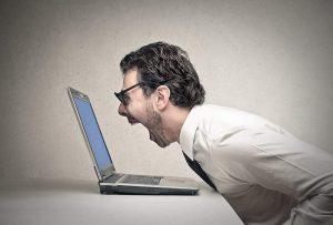 Un homme en chemise blanche entrain de potentiellement crier sur son ordinateur