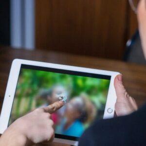 Personne utilisan Digitrack sur une tablette sur laquelle il y a une image floue
