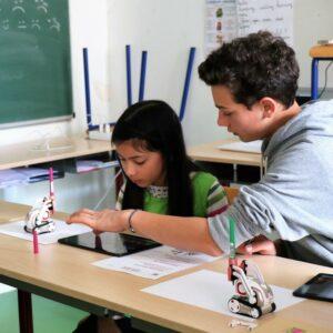 Photos de deux personnes dont une petite-fille essayant un petit robot Crocos Go Digital