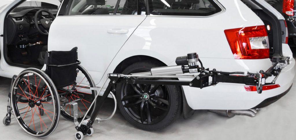 Diapo 2 : Le Wheelchair Loader avec un fauteuil sur le dispositif autour d'une voiture blanche