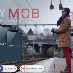 Un quai de gare avec une personne malvoyante et sa canne, EZYMOB écrit dans le ciel