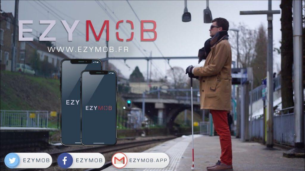 Diapo 2 : Un quai de gare avec une personne malvoyante et sa canne, EZYMOB écrit dans le ciel