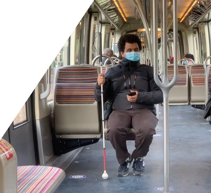 Diapo 4 : Personne malvoyante assise dans un métro avec l'application Ezymob en main sur son téléphone
