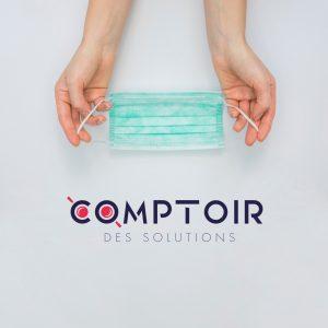 Deux mains tenants un masque chirurgicale avec le logo du Comptoir des Solutions