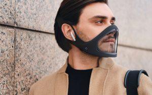 Le Masque CLIU écologique italien, sur un homme brun en trench beige et un mur gris derrière