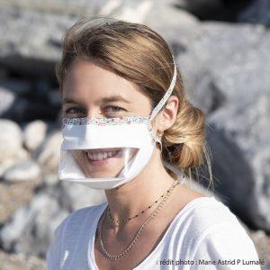 Beethoven Masque, une femme blonde souriant avec son masque transparent