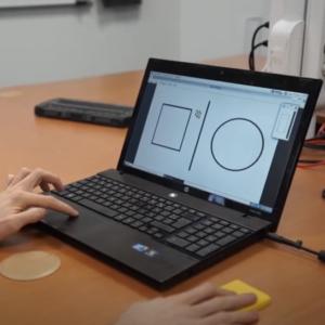 Une personne utilisant tactos avec un ordinateur et la barrette Braille