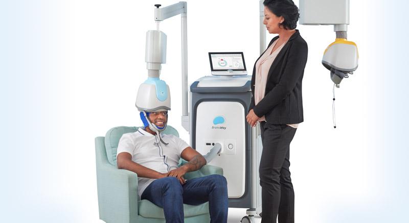 Diapo 3 : Une personne assise dans un fauteuil utilisant le casque du traitement de Brainsway avec une femme debout semblant vérifier si le traitement se passe bien