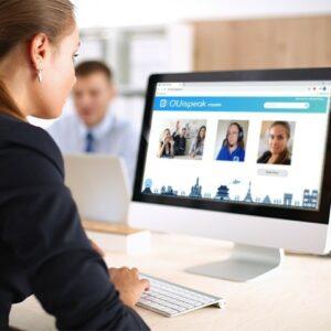 Une femme devant son ordinateur avec OUIspeak sur l'écran de l'ordinateur