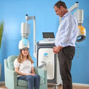 Une personne assise dans un fauteuil utilisant le casque du traitement de Brainsway avec un homme debout semblant vérifier si le traitement se passe bien