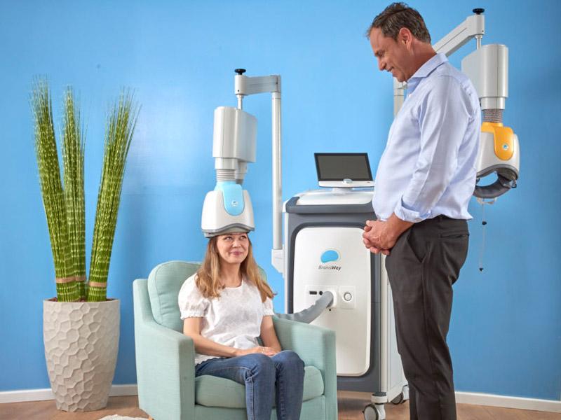 Diapo 2 : Une personne assise dans un fauteuil utilisant le casque du traitement de Brainsway avec un homme debout semblat vérifier si le traitement se passe bien