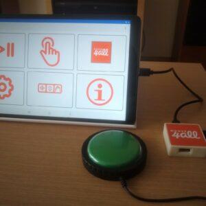 Une tablette avec l'application Mouse4All, un contacteur vert connecté au boitier sur une table en bois