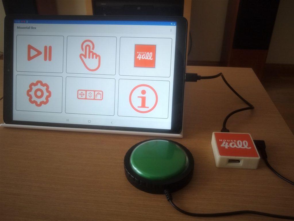 Diapo 2 : Une tablette avec l'application Mouse4All, un contacteur vert connecté au boitier sur une table en bois