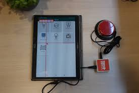 Diapo 4 : Une tablette android avec l'application Mouse4All, un contacteur rouge et le boitier de Mouse4all sur une table blanche