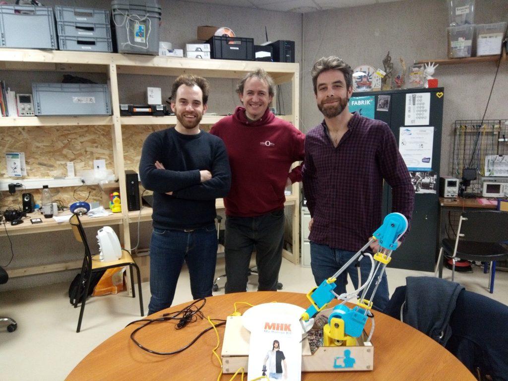 Diapo 2 : Trois personnes et le bras robotique de MakerGo, réalisé dans le fablab de My Human Kit