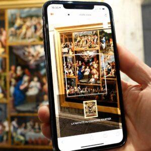 Personne utilisant l'application Livdeo au musée sur son smartphone pour la description d'un tableau