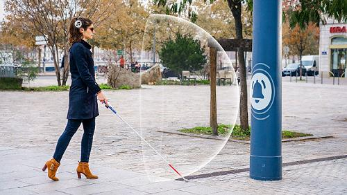 Diapo 2 : Femme qui utilise le dispositif Rango sur une canne blanche détectant un obstacle et son rayon de proximité