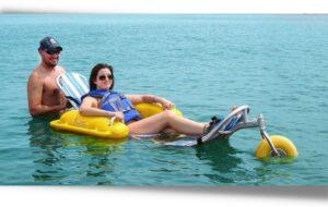 Deux personnes à la mer dont une femme à mobilité réduite sur un fauteuil roulant de plage