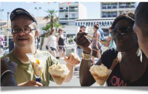 Deux personnes mangeant un glace, dont un garçon atteint d'un handicap