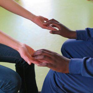Photo de deux personnes qui se touchent les mains