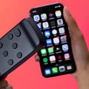 Photo des mains d'une personne tenant un smartphone dans une main et le Hable One dans l'autre