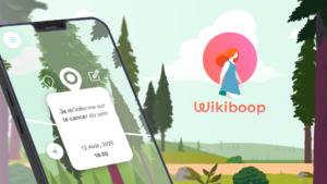 Le logo de Wikiboop, une femme sur un rond rose et un fond de paysage en dessin