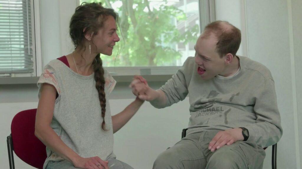 Diapo 2 : Image d'une personne en situation de handicap qui touche la main d'une femme, les deux personnes sourient