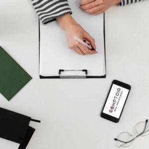 Une femme écrivant sur un bloc note avec un smartphone le logo du Comptoir