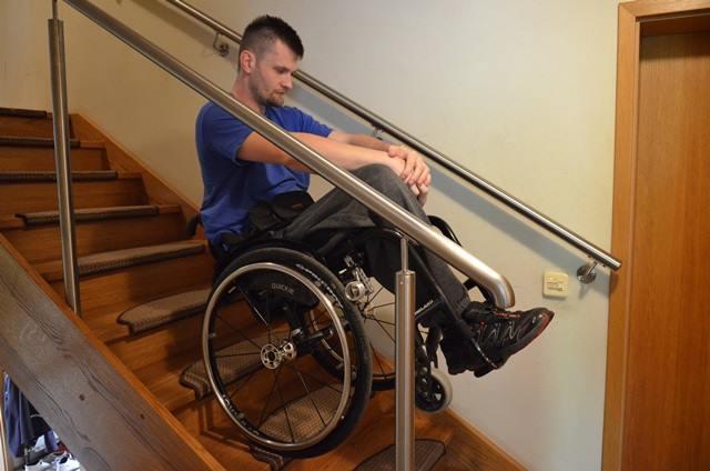Diapo 6 : Homme sur un fauteuil roulant en équilibre dans des escaliers avec des rambardes, avec le frein DEZZIV sur sa roue