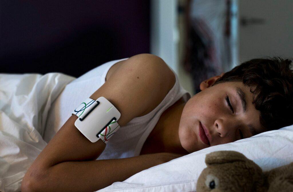 Diapo 2 : Photo d'un enfant qui dort avec le bracelet NightWatch autour de son bras