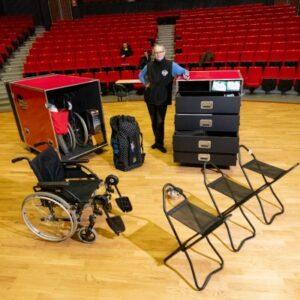 Photo d'une personne dans un théâtre avec une Handibox contenant des sièges cannes, des fauteuils roulants et d'autres matériels