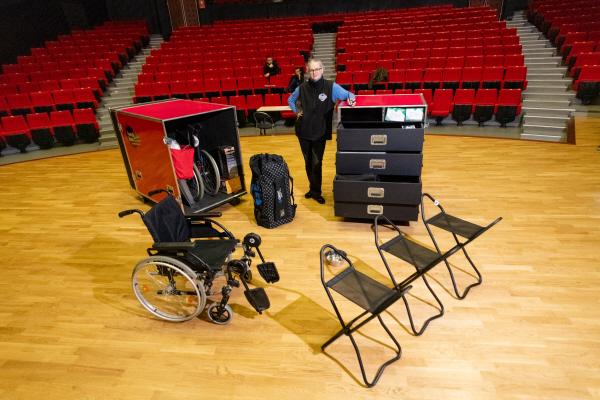 Diapo 2 : Photo d'une personne dans un théâtre avec une Handibox contenant des sièges cannes, des fauteuils roulants et d'autres matériels