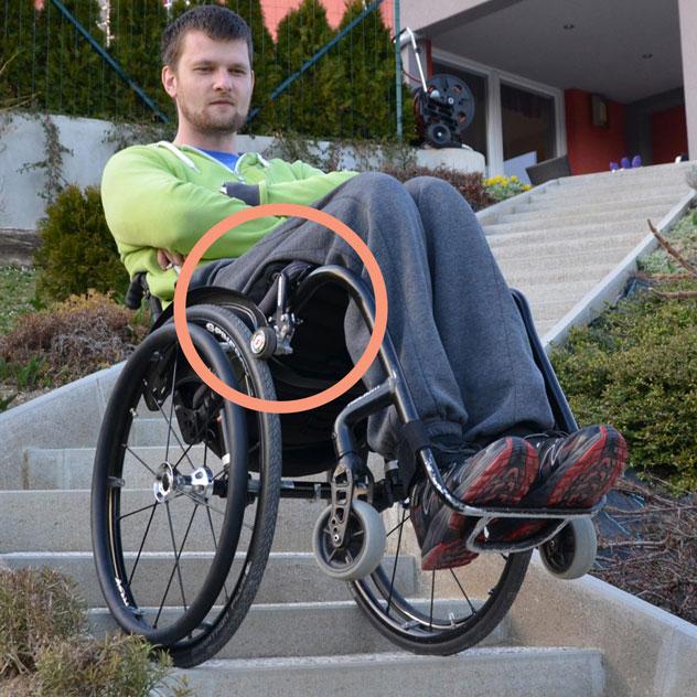 Diapo 2 : Homme sur un fauteuil roulant en équilibre dans des escaliers, avec le frein DEZZIV sur sa roue
