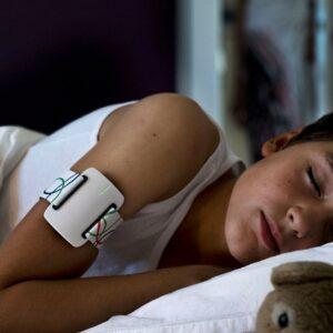 Photo d'un enfant qui dort avec le bracelet NightWatch autour de son bras