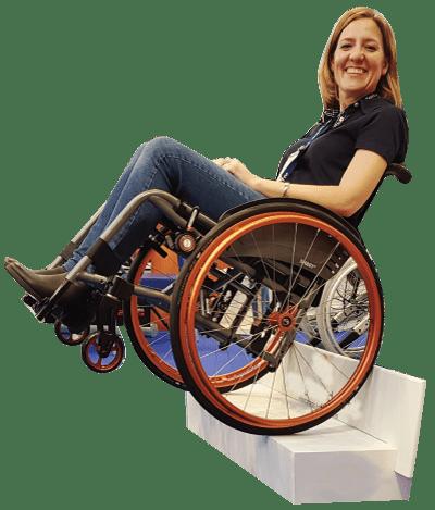 Diapo 3 : Femme sur un fauteuil roulant en équilibre sur une marche, avec le frein DEZZIV sur sa roue